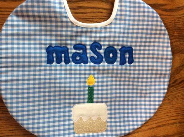 "10"" round birthday bib, first name only, with cake and candle under name shown here in blue gingham"