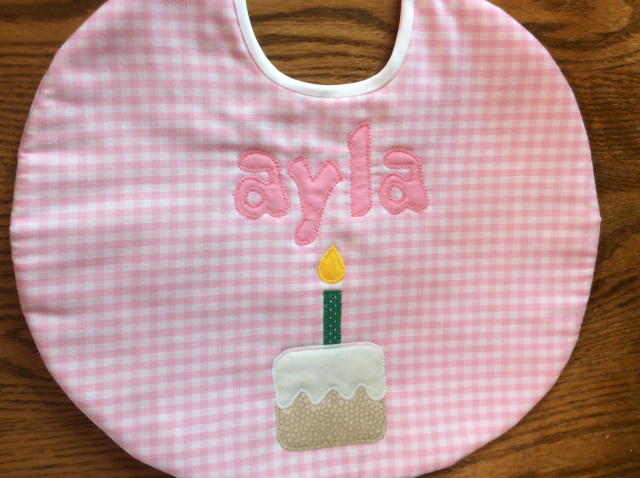 "10"" round birthday bib, first name only, with cake and candle under name shown here in pink gingham"