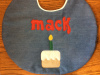 "10"" round birthday bib, first name only, with cake and candle under name shown here in medium denim"
